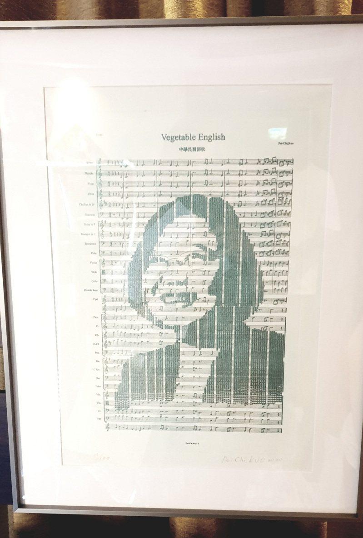 藝術家郭佩奇創作的「聲音肖像」系列,鏡框裡是用樂譜畫出的蔡英文肖像,戴上耳機可以聽到變奏的國歌,她為蔡英文、川普、陳水扁、金正恩等多位國際元首完成「聲音肖像」,每位元首都搭配一首歌。記者陳宛茜/攝影
