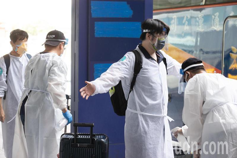 旅客通關後全部交由安排的防疫巴士接送至檢疫所集中檢疫,上車前進行消毒作業。記者季相儒/攝影