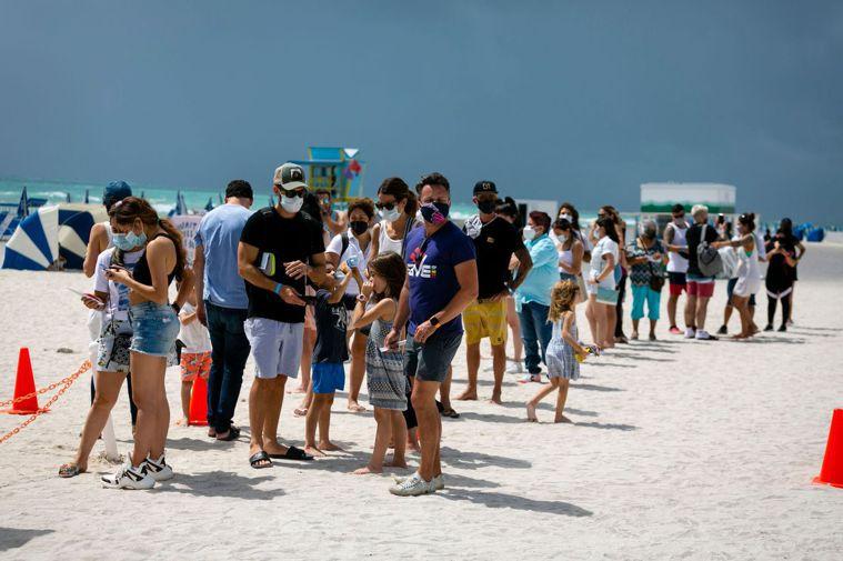 專家預期全美病例有望在夏天大幅下滑,圖為9日邁阿密一處海灘上排隊等待接種疫苗的長...