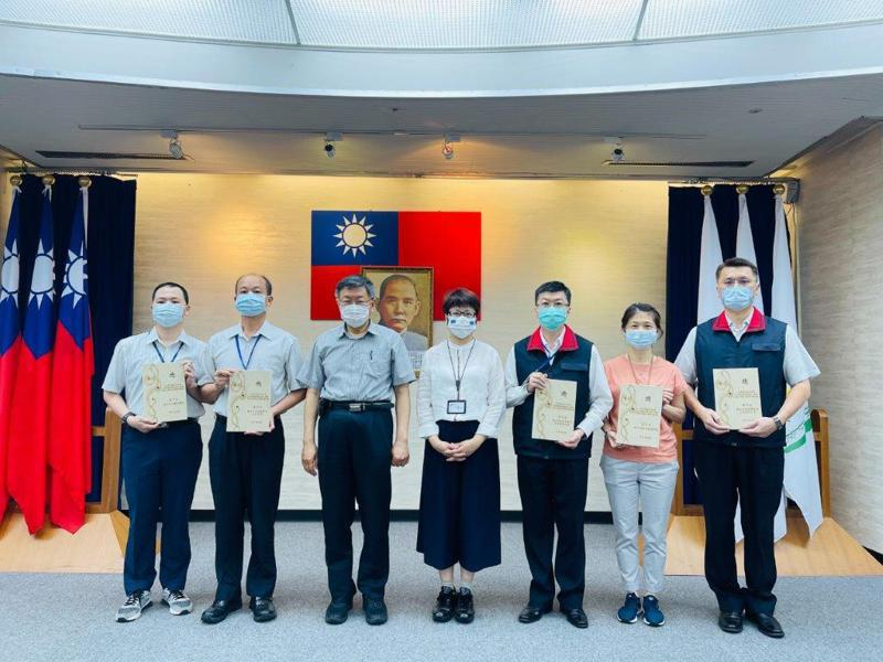 台北市長柯文哲在市政會議上,頒發採購庇護工廠產品的獎座,給績優的局處,予以表揚。  圖/北市勞動局提供