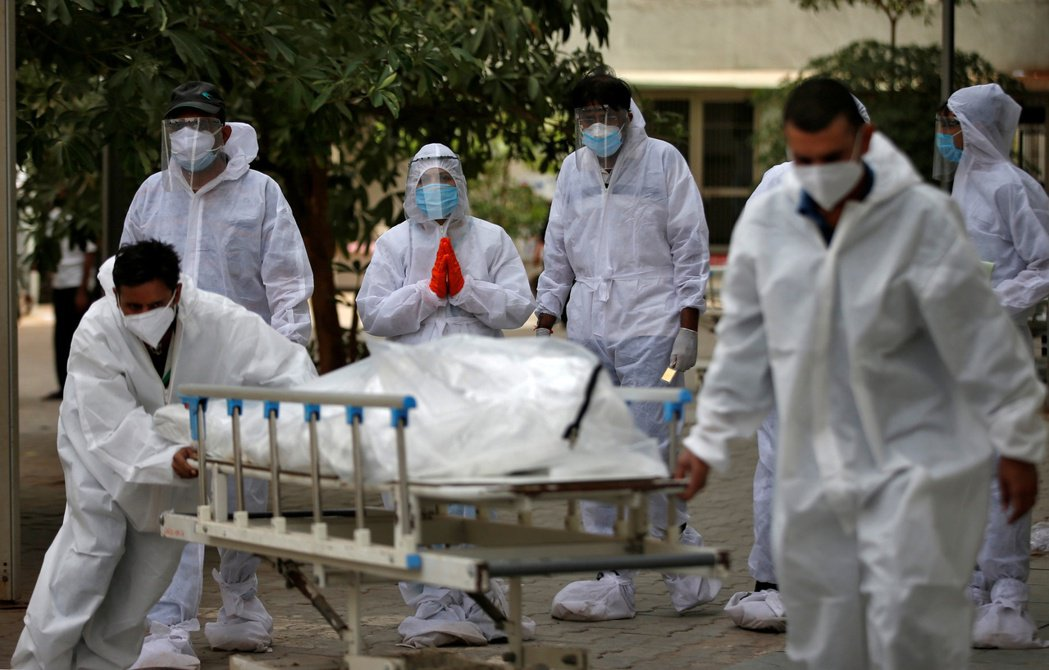 印度實際病故人數恐比官方統計高出數倍,圖為8日阿默達巴德市一具新冠病亡者遺體被推...