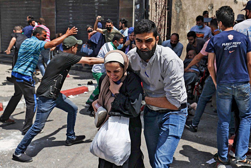 以色列在加薩地帶發動空襲,圖為當地緊急撤離的巴勒斯坦人。 圖/法新社