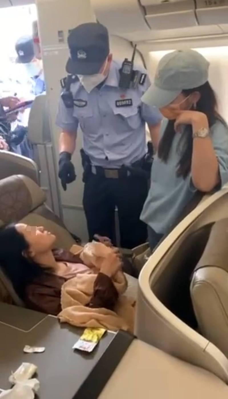 女乘客搶佔商務艙座位,警員到場勸解無果,強行帶走女乘客。(影片截圖)