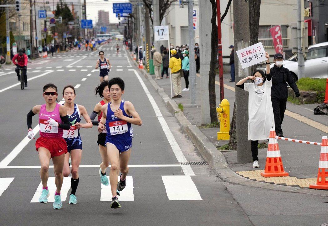 奧運馬拉松測試賽,道路旁有民眾舉起反對東奧的標語:「別搞奧運,看清現實」 圖/路...
