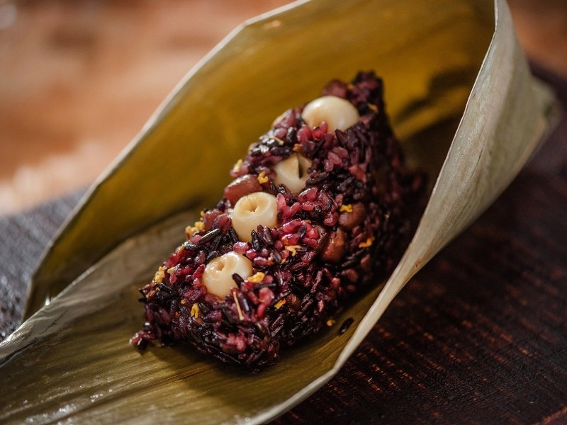 桃花林首次推出的「紫米桂香蓮子甜粽」,精選萬丹紅豆、蓮子,粽體則使用黑紫米、長糯...