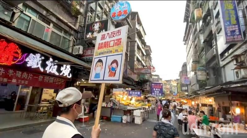 基隆廟口夜市一律戴口罩、攤商設隔板,市府人員舉牌宣導。記者游明煌/攝影