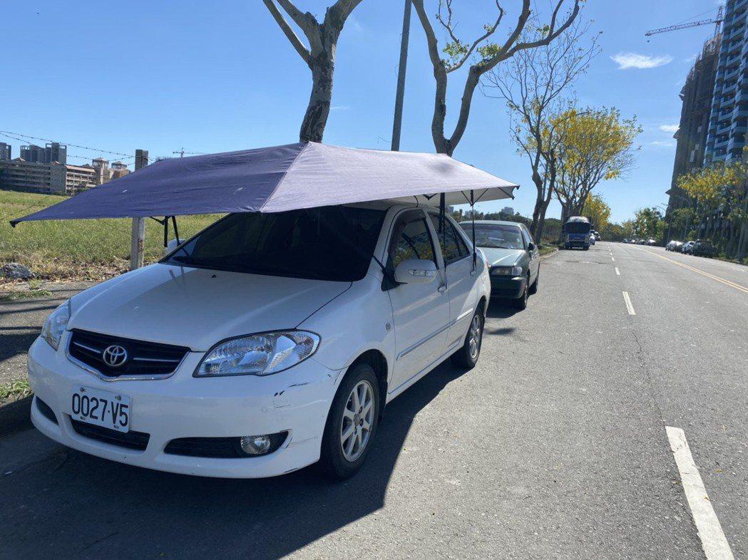 高雄連日飆高溫,路旁汽車也要撐傘防曬。記者陳弘逸/攝影