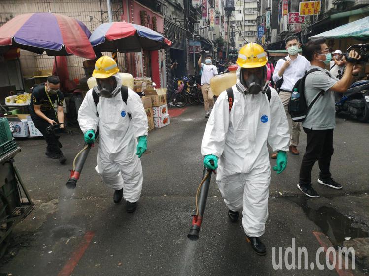 圖為昨日台北市萬華龍山寺週邊下午進行大消毒,負責清消的環保局人負全副武裝,穿著隔...