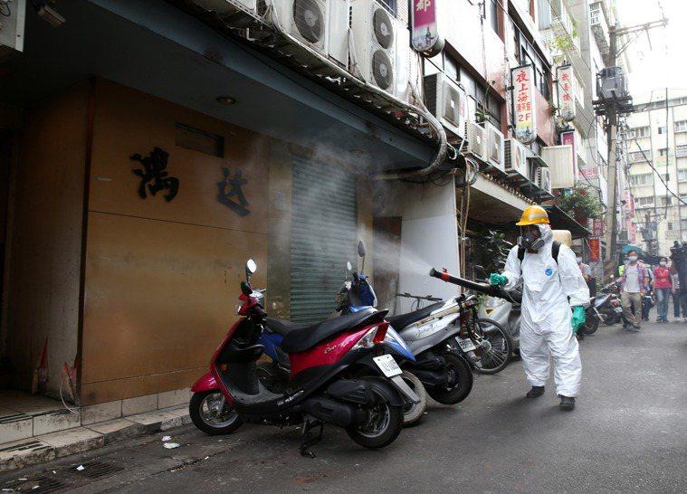 疫情拉警報,台北市萬華龍山寺週邊昨天進行大消毒,負責清消的環保局人負全副武裝,穿...