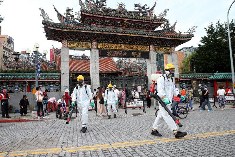 圖為台北市萬華區兩名茶藝館女員工染疫,環保局人員昨穿著隔離衣和防毒面罩,在龍山寺周邊消毒。記者邱德祥/攝影