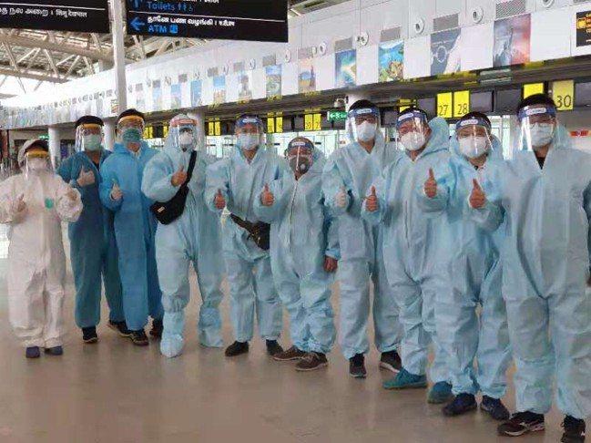 鴻海印度台籍員工在搭乘包機之前,身著防護衣在印度機場合影,顯示高規格防疫標準。讀...
