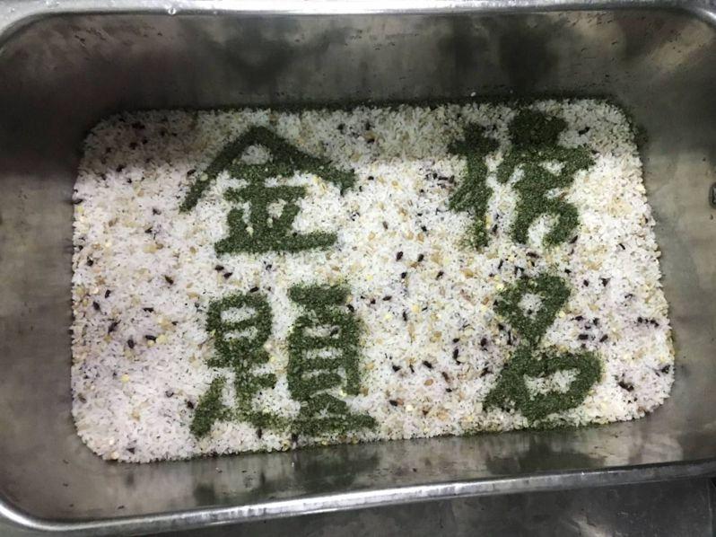台南市崇明國小中央廚房供給崇明國中三年級學生的桶飯上,以海苔鋪寫金榜題名。圖/崇明國中提供