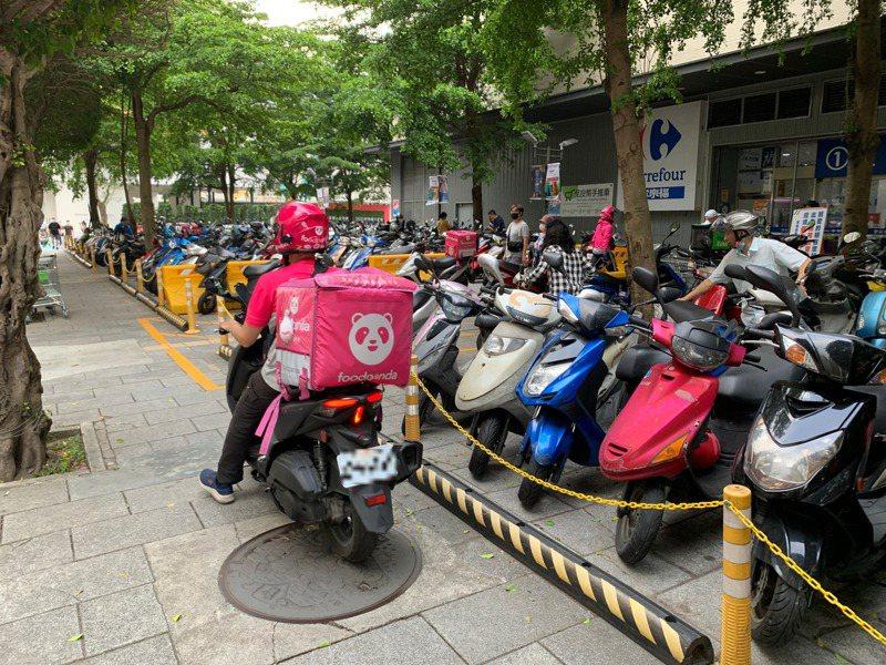外送員為加速取貨,常騎上家樂福新店店外的人行道。記者楊竣傑/攝影