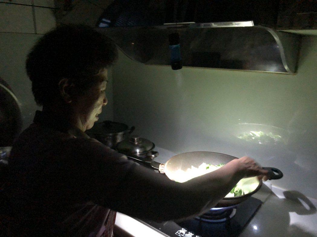 停電還是要為家人煮晚餐,有婦人拿手電筒當照明才看得到調味料,辛苦地煮完一桌料理。...