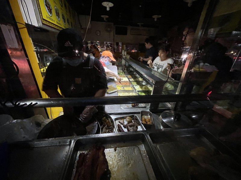 興達電廠四部機組停機,到晚上仍未恢復供電,新北賣燒臘商家摸黑切燒肉給客人吃,商家抱怨切到手指可以跟台電申請醫藥費嗎。記者陳易辰/攝影