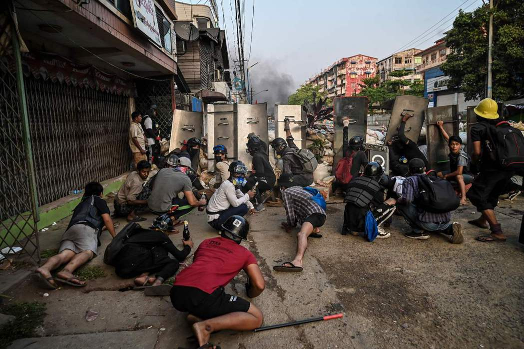 圖為3月16日,示威者在仰光拿著自製盾牌當掩護,上街抗議。 圖/法新社