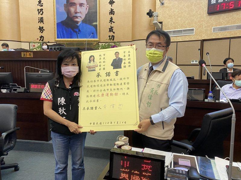民進黨台南市議員陳秋萍(左)要求台南市長黃偉哲(右)簽承諾書,允諾在市長任期內興建永康全民運動館。記者鄭維真/攝影