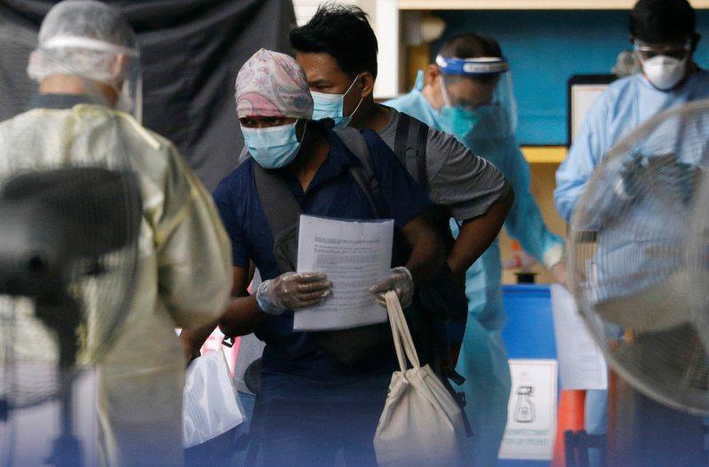 新加坡當局上月22日安排境內移工前往檢疫中心隔離。  路透