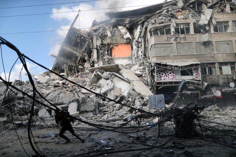 以色列軍方發射「警報火箭」打擊目標大樓屋頂,避免被控無差別殺戮和違反戰爭規範等罪行。圖為一名巴勒斯坦人在空襲期間找掩護避難。 路透