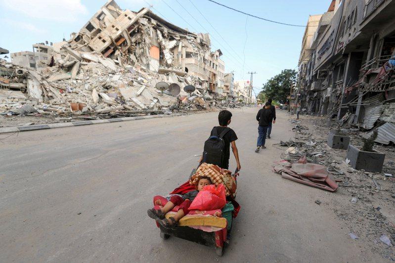 家園已毀,加薩市一名巴勒斯坦男童十四日拖著弟弟與家當,期盼能遠離砲火摧殘。(路透)