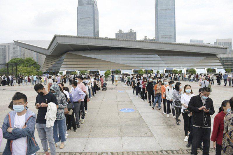 安徽省合肥市出現本土病例,市民踴躍接種新冠疫苗,圖為蜀山區奧體中心方艙接種點前大排長龍的人群。(中新社)