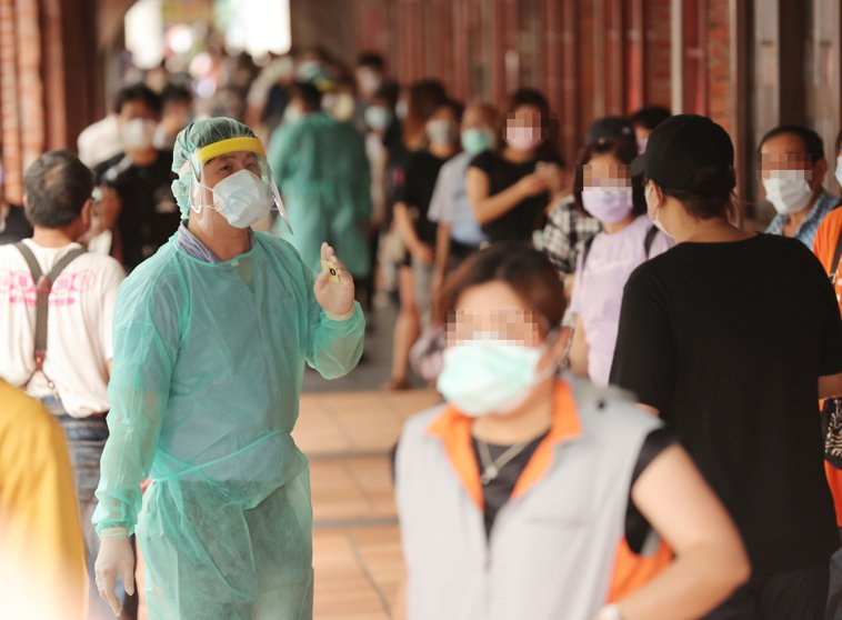 圖為台北市政府在萬華剝皮寮設立採檢站進行篩檢,不少民眾排隊等候篩檢。記者許正宏/...