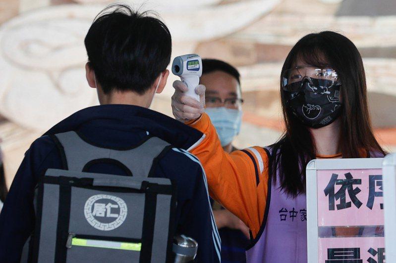 國中會考今天登場,因應國內疫情升溫,考場工作人員配戴口罩及護目鏡量測進場參加會考同學的體溫。 聯合報系記者黃仲裕/攝影