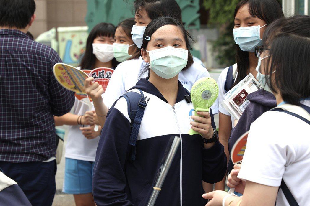 國中會考今登場,昨天考生戴起口罩手持電風扇,在炎熱的天氣和疫情威脅下看考場。記者...