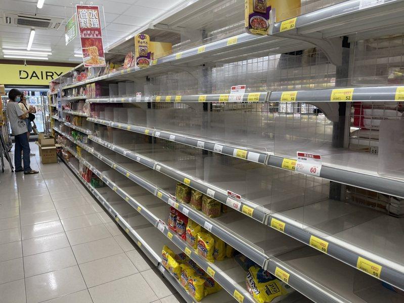 防疫期間減少外出,居家避疫較安心,不少民眾到賣場、超市採購生活物資,貨架商品被買光,工作人員頻補貨。記者劉學聖/攝影