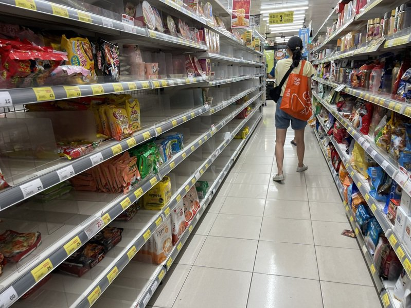 疫情升溫,不少民眾到賣場、超市採購生活物資,貨架商品被買光,工作人員頻補貨。記者劉學聖/攝影