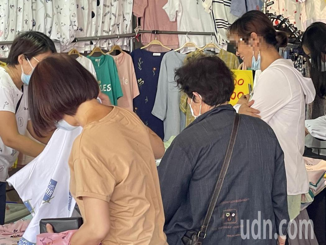 婦人逛嘉市永和市場挑選衣服,卻將口罩拉下。記者林伯驊/攝影