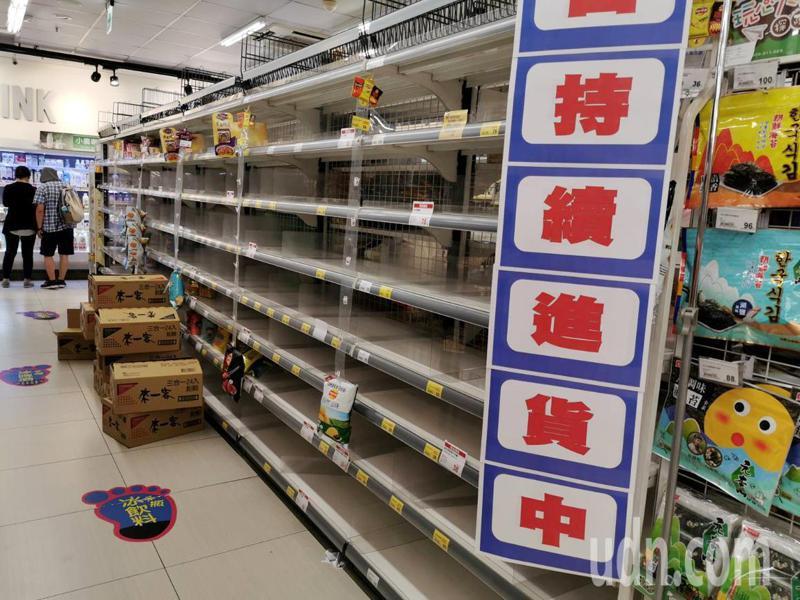 疫情擴散,桃園市多家賣場的泡麵、麵條等民生物資貨架,被搶購一空,商家貼出補貨中。記者曾增勳/攝影