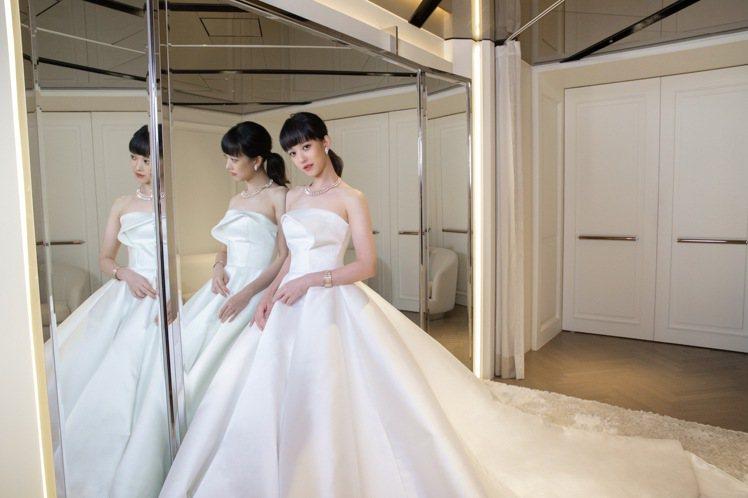 Nicole + Felicia秋冬系列的⽩⾊緞⾯長擺禮服,上⾝採⽤貼⾝俐落的剪...