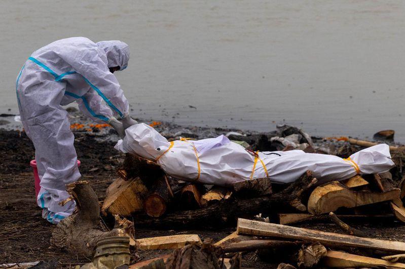 印度北方邦一名穿防護裝的男子觸碰一名死於新冠肺炎的親戚遺體,準備在恆河畔火化。(路透)