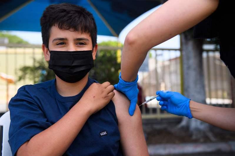 美國已開始為12-15歲的青少年打輝瑞疫苗。圖為一名13歲的青少年在洛杉磯接種輝瑞疫苗。法新社