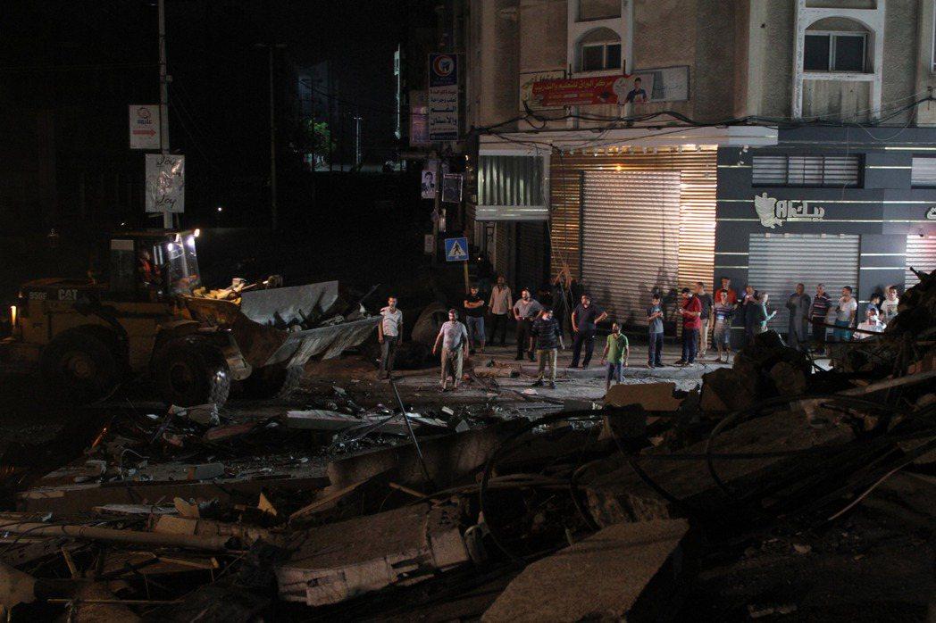 加薩當地救援人員16日在一片瓦礫廢墟中進行搜救。新華社