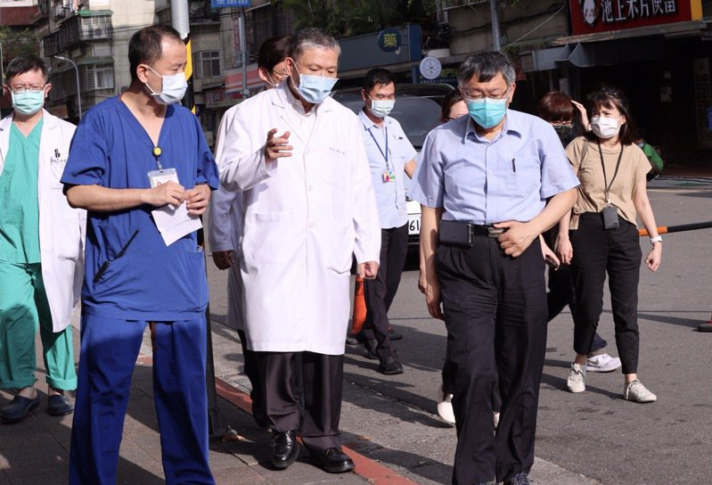 台北市長柯文哲(前右)在聯合醫院和平院區院長黃弘孟(前中)等人的陪同,視察了設在院外和平院區的快篩站,了解運作情形與人力分配情形。記者黃義書/攝影