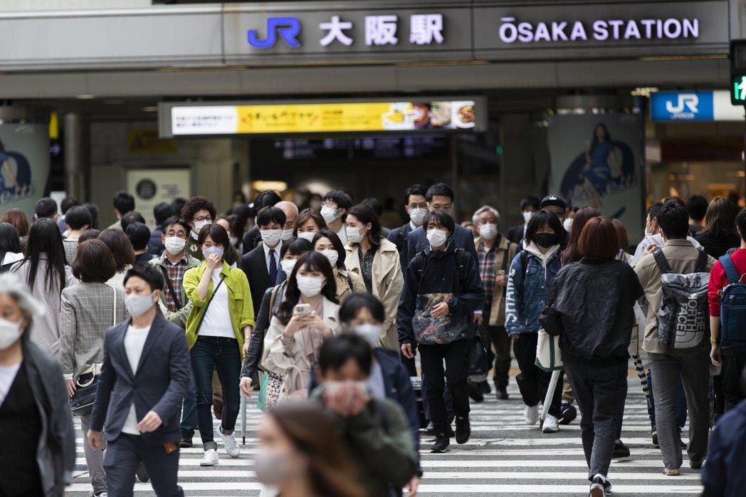 日本民眾上月十三日經過大阪車站。(美聯社)