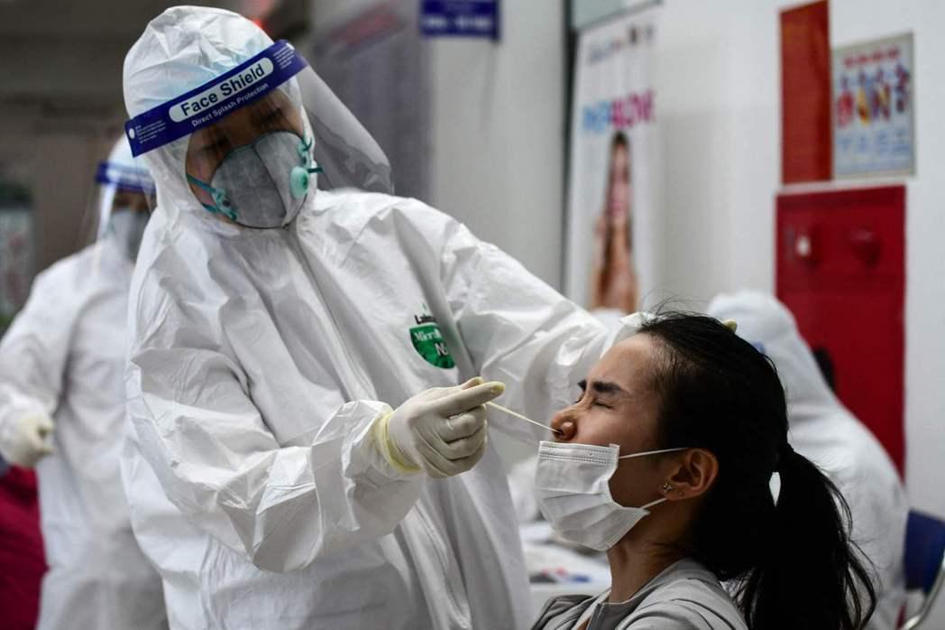 越南一名穿防護衣的醫護人員十五日在河內一間醫護中心為一名女子進行新冠病毒檢測。(...