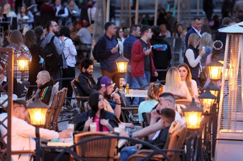 波蘭首都華沙居民十五日在城堡廣場的餐廳戶外區用餐。十五日是波蘭鬆綁防疫管制措施的首個周末,民眾無須在室外戴口罩。(歐新社)