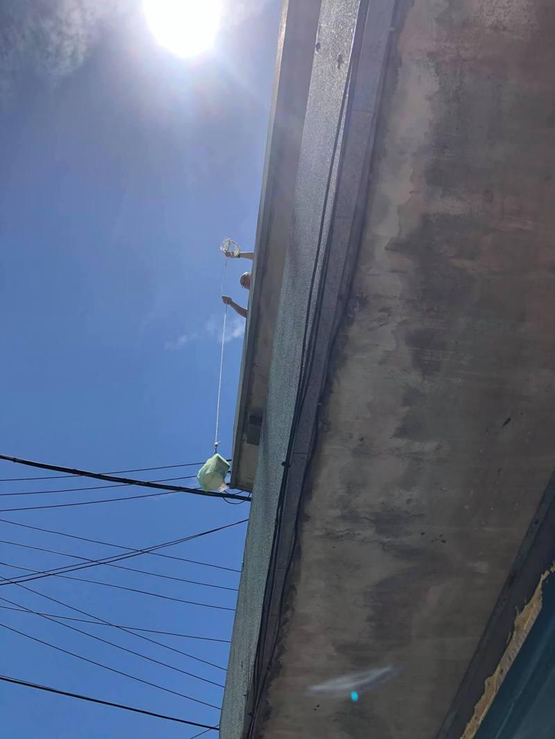 民眾利用繩索垂吊取餐。圖/取自臉書