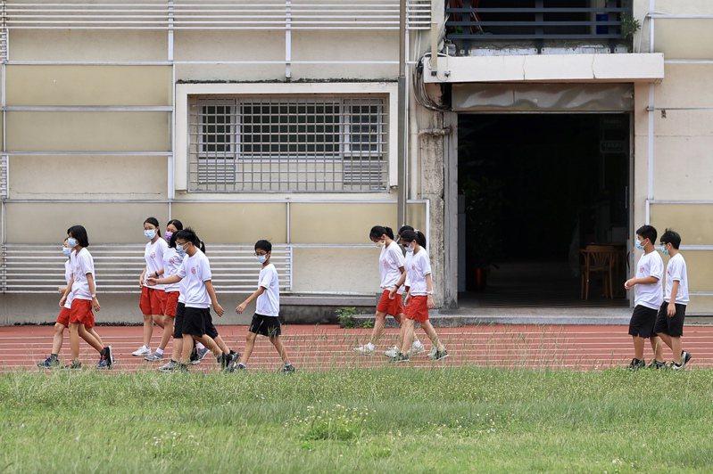 台北市、新北市今天宣布,公私立高中職、國中小、幼兒園、補習班及課後照顧中心自5月18日至28日止停課,遠距教學不到校。圖為學生帶著口罩上課。記者林伯東/攝影