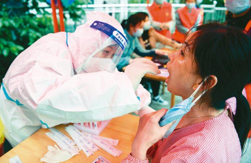 核酸檢測 一個都不能少 近日,安徽省六安、合肥等地再現新冠肺炎本土疫情,當地進行全民核酸檢測。圖為合肥市肥西縣上派鎮一個小區,居民接受核酸檢測。(新華社)