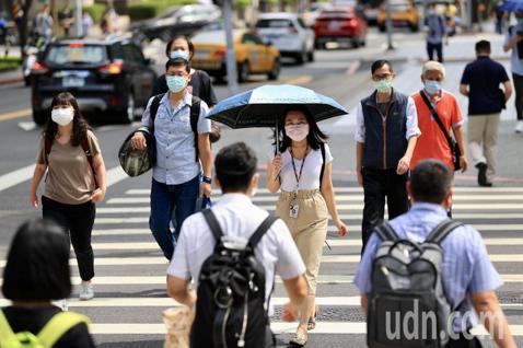 疫情警戒後升級,民眾上班途中就算在室外也全程戴著口罩。 圖/記者林伯東攝影