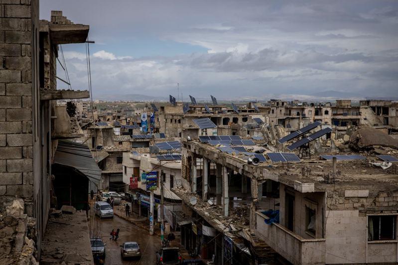在敘利亞北部伊德利卜省本尼什鎮,許多難民入住曾遭政府軍轟炸的破敗樓房,那些房子的屋頂,現在都有太陽能板。圖/取自紐約時報