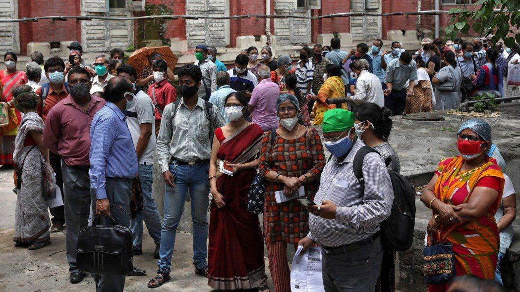印度加爾各答民眾排隊等候接種新冠疫苗。路透