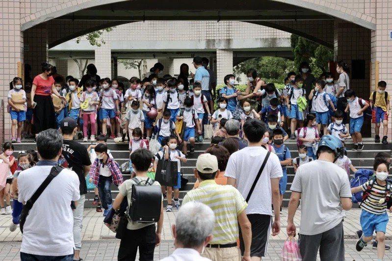 疫情持續擴大,雙北高中以下學校停課,台北市博愛國小中午低年級學生下課,不少家長前來將小朋友接回家。記者許正宏/攝影