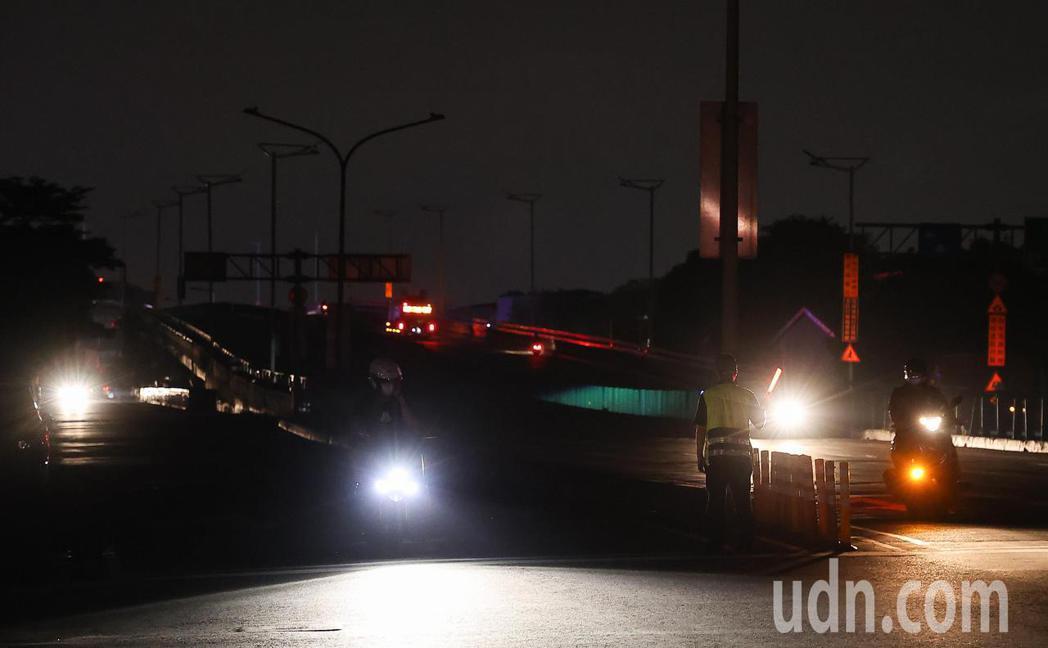 台電今晚再度無預警通知輪流限電,台北市民權大橋下內湖一帶一片漆黑,警察趕緊出動指...