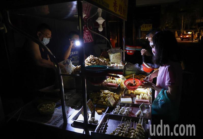 台電今晚再度無預警通知輪流限電,讓許多商家措手不及,台北市內湖一間鹹酥雞店拿著手電筒摸黑繼續做生意。記者余承翰/攝影