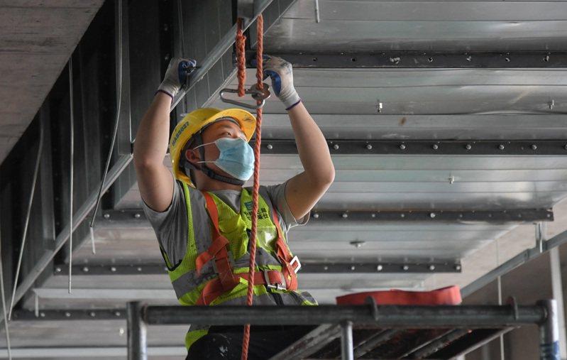 圖為工人戴口罩施工示意圖,非新聞當事人。 新華社